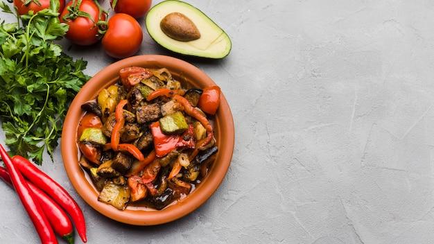 Вкусная еда на тарелке среди овощей