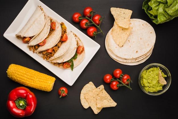 野菜とソースの近くの皿の上のタコス