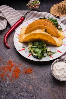 チリとナプキンのソースの近くの皿に野菜の中でタコス