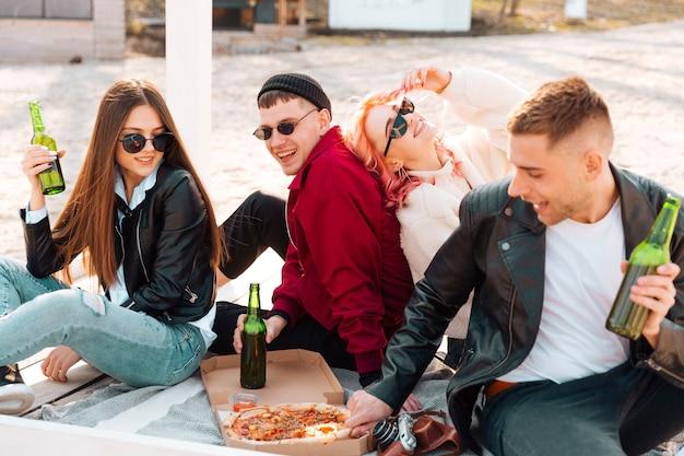 地面に座ってパーティーを持つ幸せな友達