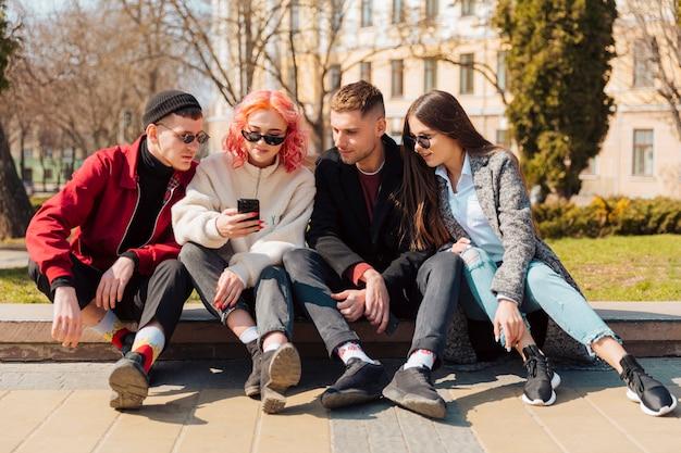 Молодые люди сидят на бордюре и смотрят на смартфон