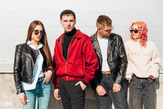 Молодые люди в модной одежде позирует на улице