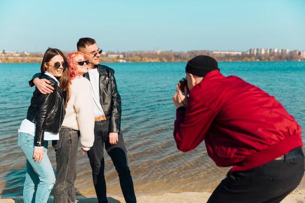 若い男が面白い友達の写真を撮る