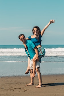 Счастливые влюбленные веселятся на песчаном пляже летом
