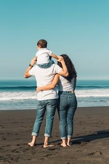 Отец держит ребенка на шее и обнимает с женой на пляже