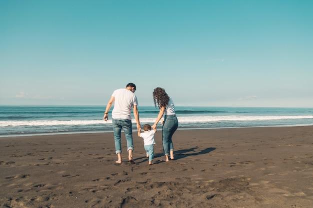 ビーチで楽しんで赤ちゃんと一緒に幸せな家族