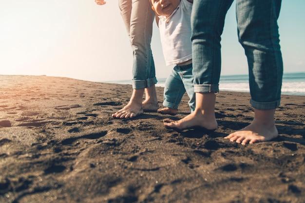 Улыбающийся ребенок делает первые шаги с родителями на солнечном пляже