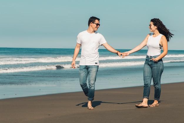 ロマンチックなカップルは太陽が降り注ぐビーチの上を歩く