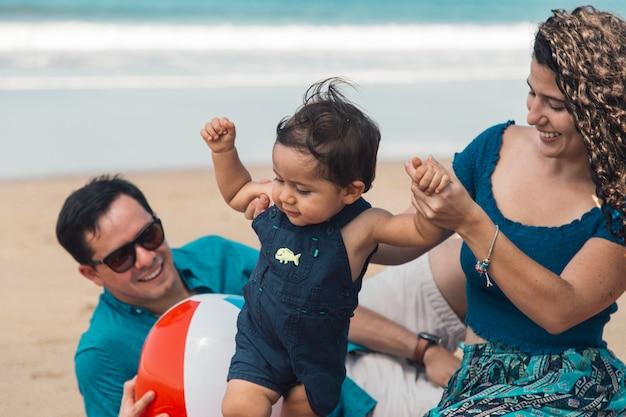 海辺で母親と一緒に第一歩を踏み出す赤ちゃん