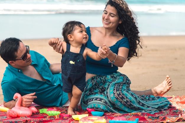 幸せな家族が遊んで、ビーチの上を歩くことを学ぶ赤ちゃん