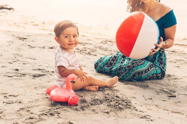Малыш с мамой, играя на пляже