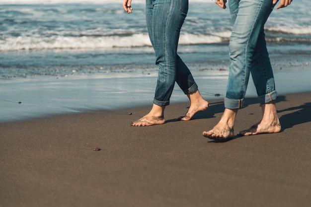 海に沿って散歩するカップルの足