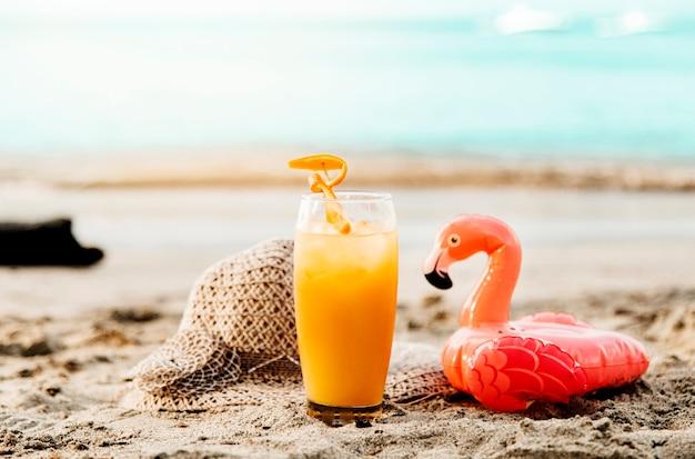 オレンジ色の飲み物と砂の上のおもちゃのフラミンゴ
