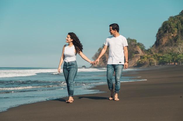 空のビーチを歩いている若いカップル