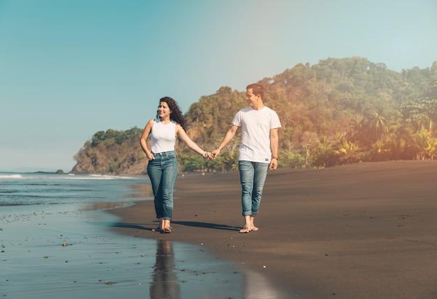 幸せなカップルが海辺を散歩