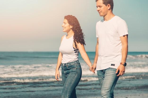 晴れた日に海に沿って歩くカップル