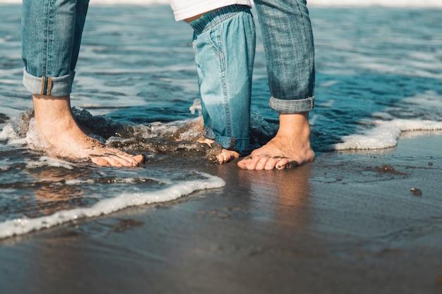 家族でビーチで濡れた砂の上に裸足で立っています。