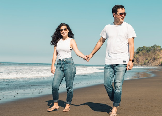 砂浜のビーチで裸足で歩くカップル
