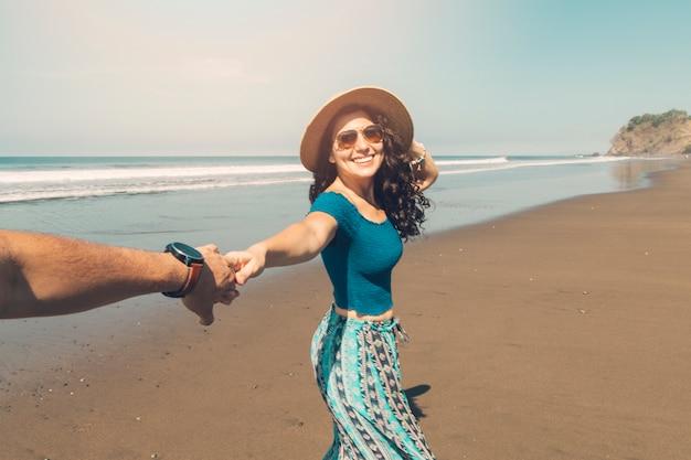 Пара гуляя вдоль берега моря