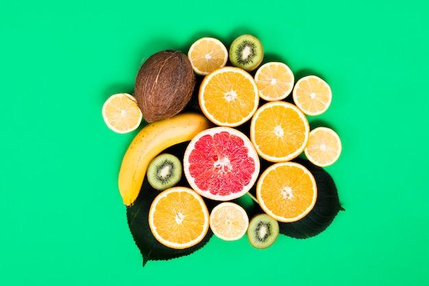 緑色の背景で混合カラフルなトロピカルフルーツの配置
