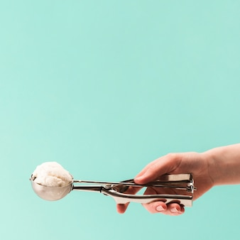 Рука из нержавеющей совок с вкусным ванильным мороженым