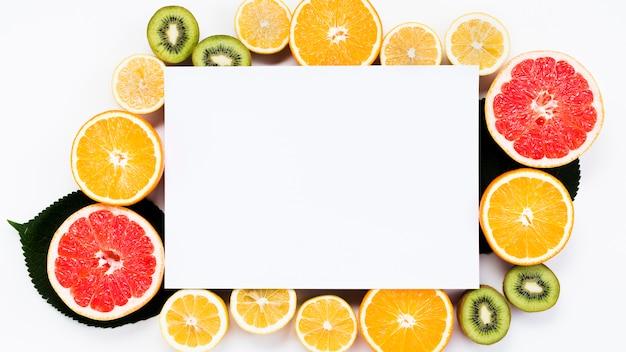 空白の紙とスライスされたカラフルなトロピカルフルーツの配置