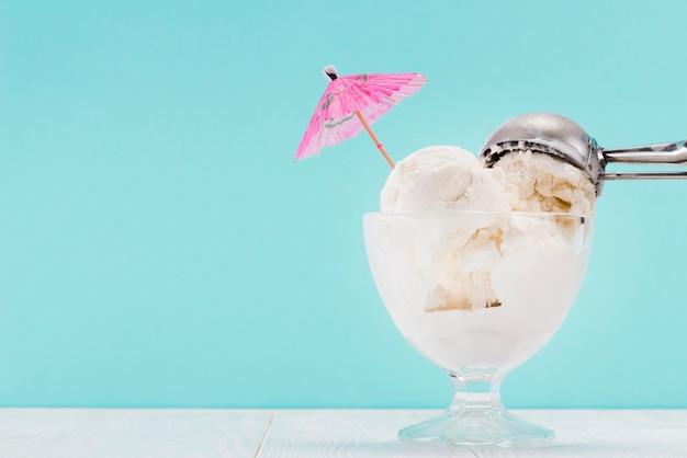 ガラスの花瓶と上に金属のスプーンでアイスクリーム