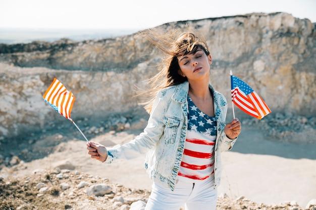 目を閉じてアメリカの国旗を保持している女性