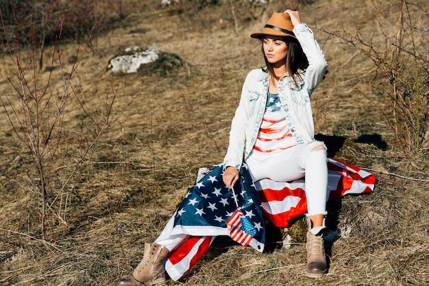 自然の中で座っているアメリカの国旗を持つ女性