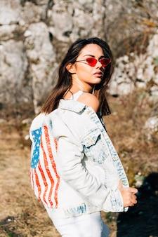 Крутая молодая женщина в джинсовой куртке и солнцезащитных очках