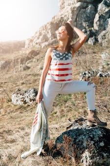 デニムジャケットと石の上に立っているトレンディな女性