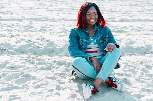 砂の上に座って足を交差を持つアフリカ系アメリカ人女性