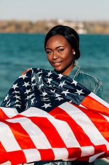 アメリカの国旗を保持している黒人女性