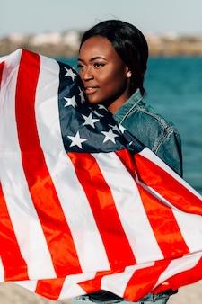 アフリカ系アメリカ人の女性が顔にもたれてアメリカの国旗を保持