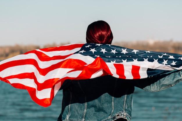 女性は立ってアメリカの国旗を保持して引き返した
