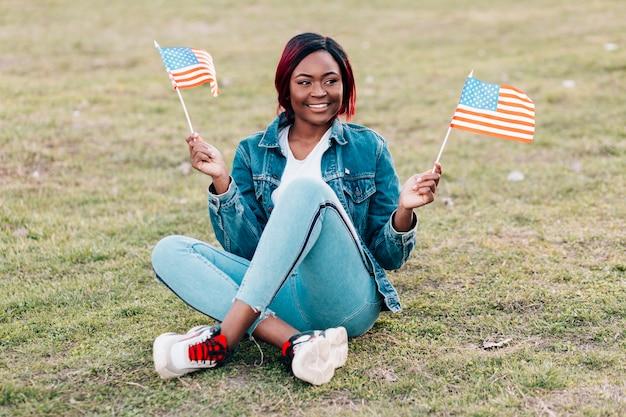 草の上に座ってアメリカ国旗を持つ黒人女性