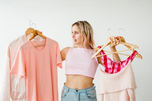 Светловолосый влияющий держит розовую одежду