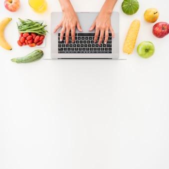 Вид сверху ноутбук в окружении фруктов