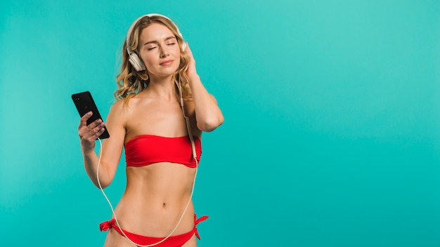 ヘッドフォンで音楽を聴くビキニの若い女性
