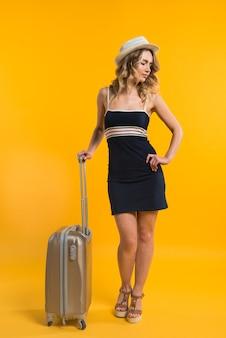 飛行を待っているスーツケースを持つ若い女