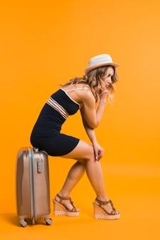 Утомленная молодая женщина сидя на чемодане в студии