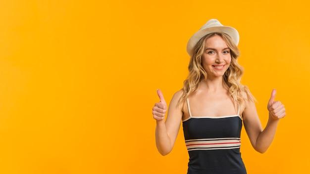 Улыбается женщина в летней одежде, показывает палец вверх
