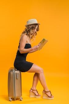 Женщина сидит на чемодане и изучает карту