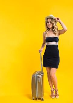 Счастливая молодая женщина с чемоданом, глядя