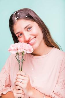 ブルネットの少女は花とポーズ