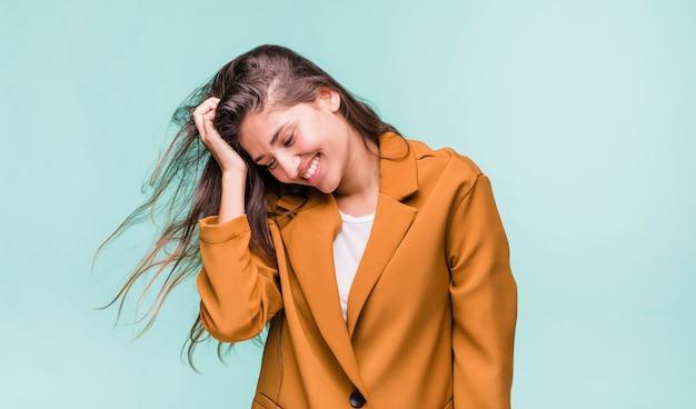 Улыбающаяся девушка брюнетка позирует с пальто