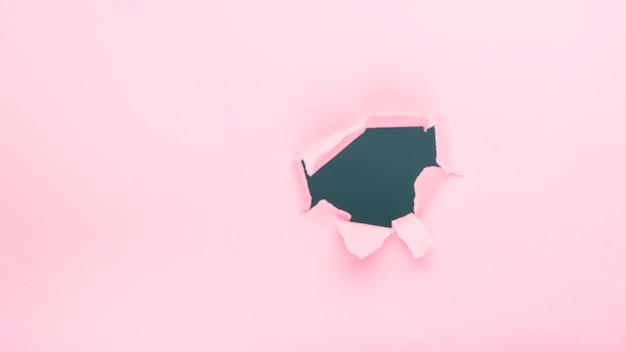 Отверстие на розовой бумаге