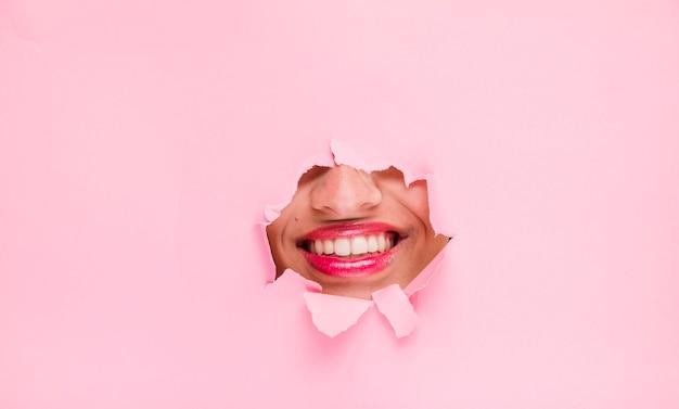 紙の穴を通してポーズブルネットの少女