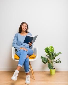 本を読んで座っているブルネットの少女