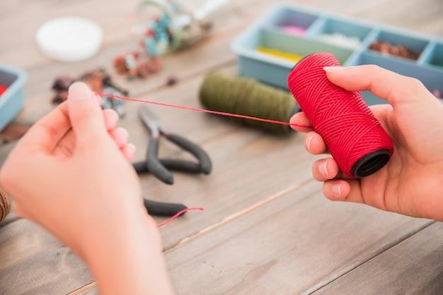 木製の机の上の赤い糸のスプールを持っている人の手のクローズアップ